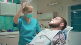 Den kvinnliga tandläkaren sitter ner och undersökande tänder av den manliga patienten arkivfilmer