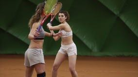 Den kvinnliga tennislagledaren visar tekniken av kuggen med racket till en härlig lång haired flicka på tennisbanan stock video