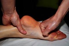 Den kvinnliga terapeuten ger massage f?r h?ger fot royaltyfria foton