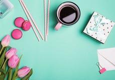 Den kvinnliga tillbehören och rosa tulpan på pastell gör grön bakgrund royaltyfri fotografi