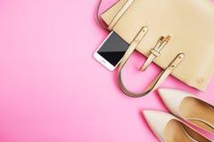 Den kvinnliga tillbehören sänker lekmanna- Smartphone för kvinnaskopåse på rosa bakgrund Beige färgkvinnatillbehör Textutrymme To Arkivbild