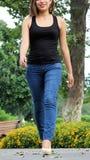 Den kvinnliga tonåringen och jeans för skönhet som bärande in går, parkerar Royaltyfri Bild