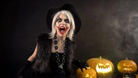 Den kvinnliga trollkvinnan med grått hår skrämmer, trollar, gjuter ett pass Den läskiga härliga flickahäxan firar halloween med arkivfilmer