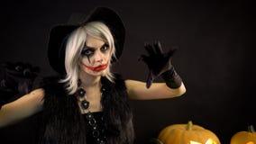 Den kvinnliga trollkvinnan med grått hår skrämmer, trollar, gjuter ett pass Den läskiga härliga flickahäxan firar halloween med stock video