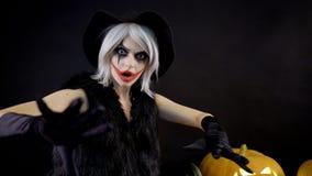 Den kvinnliga trollkvinnan med grått hår skrämmer, trollar, gjuter ett pass Den läskiga härliga flickahäxan firar halloween med lager videofilmer