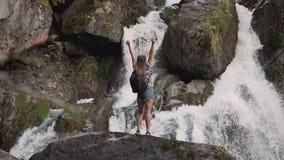 Den kvinnliga turisten med en ryggsäck lyfter upp hans händer mitt emot ett stort vattenfallanseende på kanten av en klippa Lyckl stock video