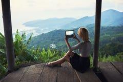 Den kvinnliga turisten skjuter videoen på den digitala minnestavlan av ett härligt djungellandskap royaltyfri foto