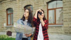 Den kvinnliga turisten tar foto, medan hennes attraktiva flicka för vännen ser översikten och visar hennes riktningsanseende in stock video