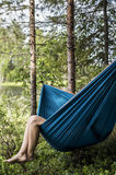 Den kvinnliga turisten vilar i en hängmatta i skogen, på en blurr Royaltyfri Fotografi