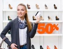 Den kvinnliga visningkreditkorten i skodon shoppar Royaltyfri Bild