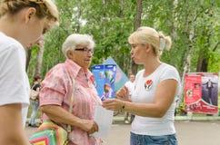 Den kvinnliga volontären förklarar till äldre kvinnamätningar av kroppsfettmätningsbildskärmen och gör rekommendationer för sunt arkivfoto