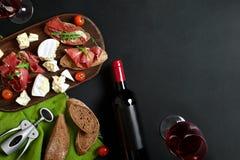 Den läckra aptitretaren till vin - skinka, ost, bagettskivor, tomater, tjänade som på ett träbräde och exponeringsglas med rött v arkivbild