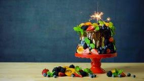 Den läckra chokladdroppandekakan dekorerade med nya säsongsbetonade frukt och bär arkivfilmer