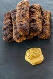 Den läckra grillade romanian för mititei för ori för köttfärsrullar mici traditionella och balkan maträtten tjänade som med senap Royaltyfria Foton