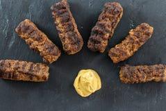 Den läckra grillade romanian för mititei för ori för köttfärsrullar mici traditionella och balkan maträtten tjänade som med senap Arkivbilder