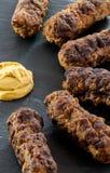 Den läckra grillade romanian för mititei för ori för köttfärsrullar mici traditionella och balkan maträtten tjänade som med senap Royaltyfria Bilder
