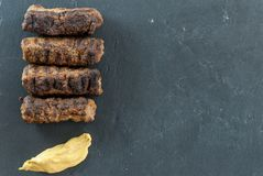 Den läckra grillade romanian för mititei för ori för köttfärsrullar mici traditionella och balkan maträtten tjänade som med senap Royaltyfri Bild