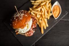 Den läckra hamburgaren med fransman steker på mörk bakgrund Skjutit i en studio royaltyfria foton