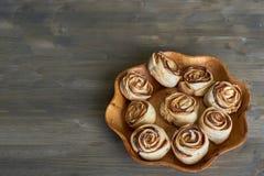 Den läckra och sötsaken bakade rosen formade bakelse med äpplefyllning på den träblomman formade plattan på träbakgrund Royaltyfri Foto