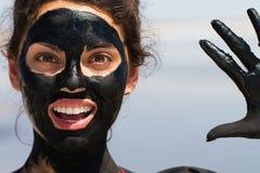 Den läkande gyttjan på huden av en härlig ung flicka Arkivfoton