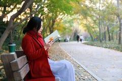Den läs- naturen är in min hobby, den flicka lästa boken sitter bänken Fotografering för Bildbyråer
