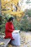 Den läs- naturen är in min hobby, den flicka lästa boken sitter bänken Arkivbilder