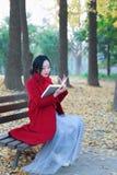 Den läs- naturen är in min hobby, den flicka lästa boken sitter på bänken Royaltyfria Bilder