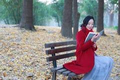 Den läs- naturen är in min hobby, den flicka lästa boken sitter på bänken Arkivfoto