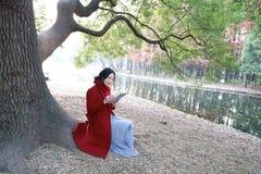 Den läs- naturen är in min hobby, den flicka lästa boken sitter under stort träd Fotografering för Bildbyråer