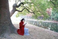 Den läs- naturen är in min hobby, den flicka lästa boken sitter under stort träd Royaltyfria Foton