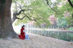 Den läs- naturen är in min hobby, den flicka lästa boken sitter under stort träd Royaltyfri Fotografi