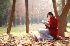 Den läs- naturen är in min hobby, den flicka lästa boken sitter under stort träd Arkivfoto