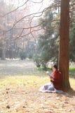 Den läs- naturen är in min hobby, den flicka lästa boken sitter under träd Arkivfoto