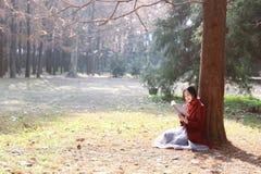 Den läs- naturen är in min hobby, den flicka lästa boken sitter under träd Arkivbild