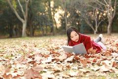 Den läs- naturen är in min hobby, den flicka lästa boken som mycket ligger på av lönnlöv Arkivbild
