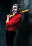 Den läskiga clownen och baseball-slagträet på dackbakgrund för den grymma säger miniatyrreaperen halloween för kalenderbegreppsda Royaltyfri Fotografi
