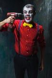Den läskiga clownen och den elektriska drillborren på dackbakgrund för den grymma säger miniatyrreaperen halloween för kalenderbe Arkivfoto