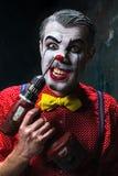 Den läskiga clownen och den elektriska drillborren på dackbakgrund för den grymma säger miniatyrreaperen halloween för kalenderbe Royaltyfria Bilder
