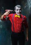 Den läskiga clownen och den elektriska drillborren på dackbakgrund för den grymma säger miniatyrreaperen halloween för kalenderbe Royaltyfri Fotografi