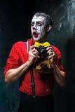 Den läskiga clownen och en kamera på dackbakgrund för den grymma säger miniatyrreaperen halloween för kalenderbegreppsdatumet lyc Royaltyfria Bilder