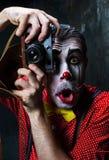 Den läskiga clownen och en kamera på dackbakgrund för den grymma säger miniatyrreaperen halloween för kalenderbegreppsdatumet lyc Royaltyfria Foton