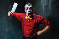 Den läskiga clownen som rymmer en kniv på dack för den grymma säger miniatyrreaperen halloween för kalenderbegreppsdatumet lyckli Arkivbilder