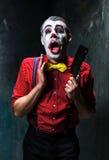Den läskiga clownen som rymmer en kniv på dack för den grymma säger miniatyrreaperen halloween för kalenderbegreppsdatumet lyckli Royaltyfria Bilder