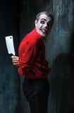Den läskiga clownen som rymmer en kniv på dack för den grymma säger miniatyrreaperen halloween för kalenderbegreppsdatumet lyckli Royaltyfria Foton