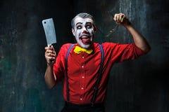 Den läskiga clownen som rymmer en kniv på dack för den grymma säger miniatyrreaperen halloween för kalenderbegreppsdatumet lyckli Royaltyfri Foto