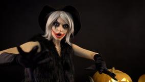 Den läskiga härliga flickahäxan firar halloween med roliga glödande brinnande pumpor i rök Kvinna med grått hår arkivfilmer