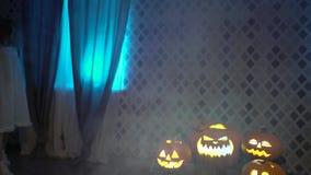 Den läskiga levande dödflickan i nattlinne med yxan söker efter offret, firar halloween med roliga ilskna skrämmande pumpor lager videofilmer