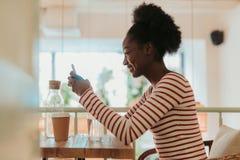 Den låga vinkeln av lyckliga afrikanska kvinnan som den har, vilar i kafé fotografering för bildbyråer
