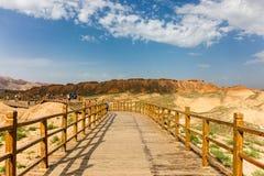 Den långa bockbron i Danxia parkerar, blomstra för moln för himmel vitt arkivbild