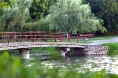 Den långa bron med röda stänger över floden i stad parkerar Royaltyfri Bild